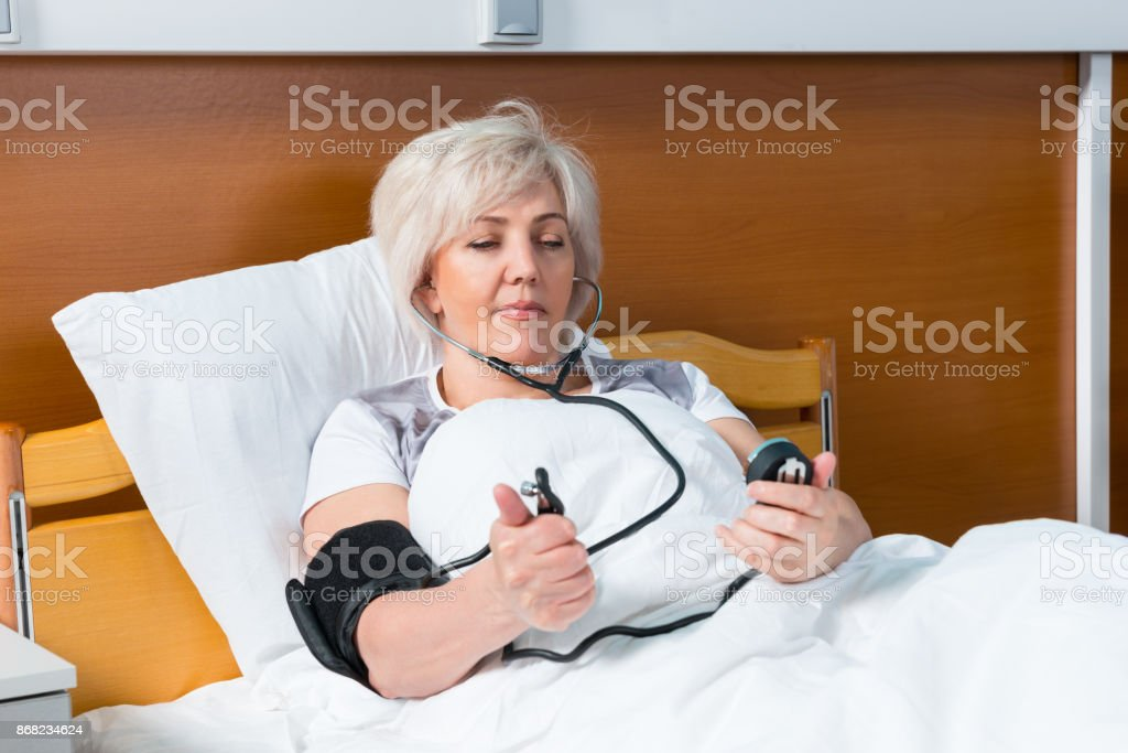 Female patient is measuring the arterial pressure using a medical equipment, while lying in the hospital bed stock photo