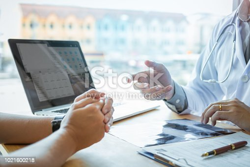 1026367516 istock photo Female patient listening to doctor at desk and consulting with healthcare in hospital. 1021600218