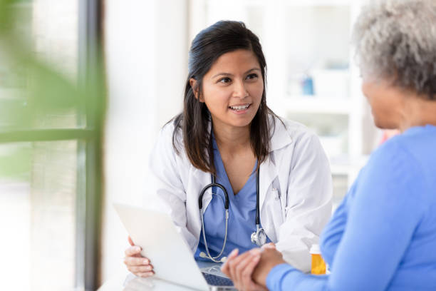 Female patient listens carefully to mid adult female doctor stock photo