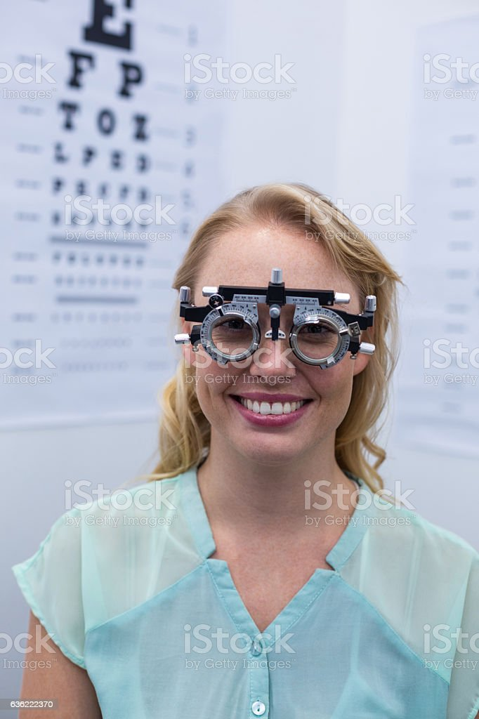 Female patient looking through messbrille during eye examination stock photo
