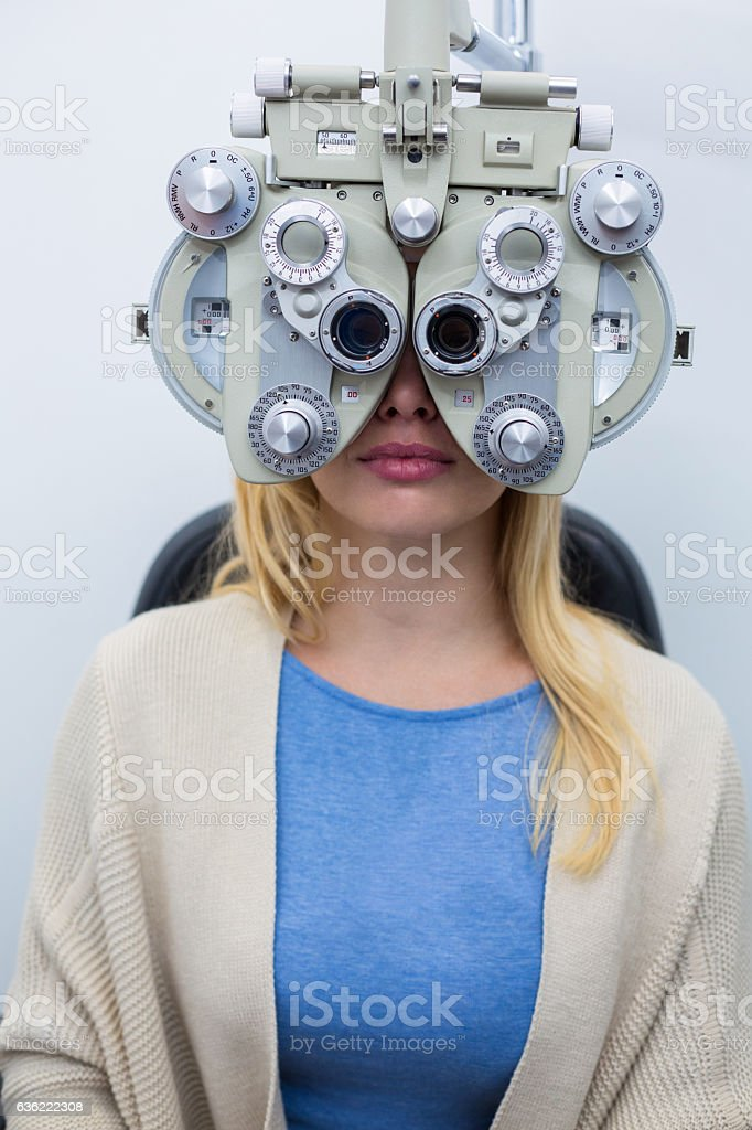 Female patient looking through phoropter during eye examination stock photo
