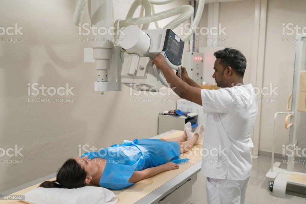 Weibliche Patienten liegen bereit für ein Xray und Radiologen immer bereit die Maschine – Foto