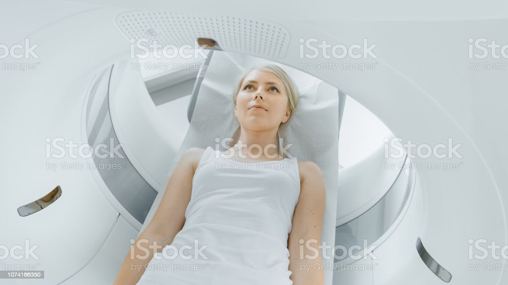 Female Patient Lying On A Ct Or Mri Scan Bed Is Moving