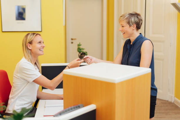 Female patient making payment at a dental surgery stock photo