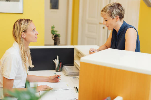 Female patient registering at a medical reception stock photo
