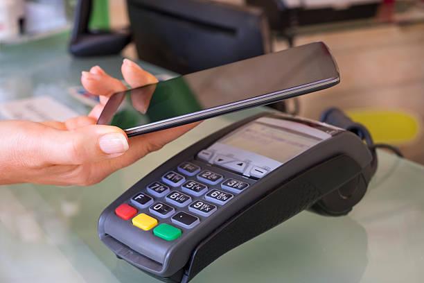 Frau bezahlen mit NFC-Technologie auf Handy, Kosmetikerin – Foto