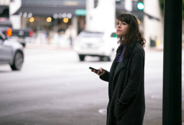 Female Pedestrian Waiting with Cellphone for a Ride Share stock photo