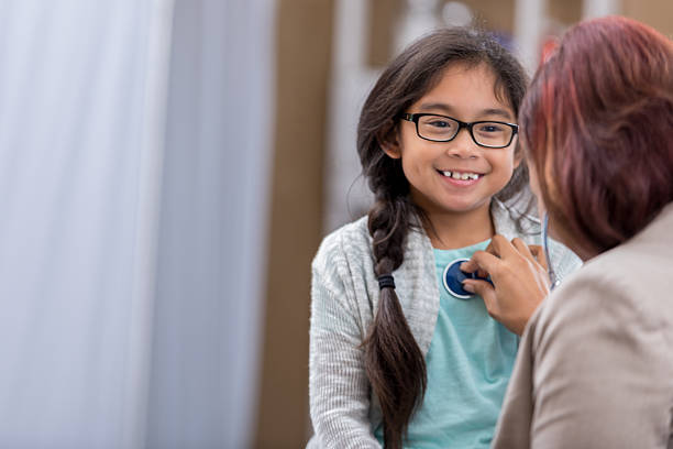 Female pediatrician listens to young patient's heartbeat stock photo