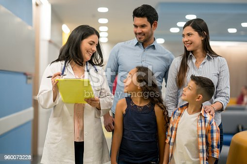 Female pediatrician talking to her sweet patient while brother and parents listen to them all smiling looking very happy