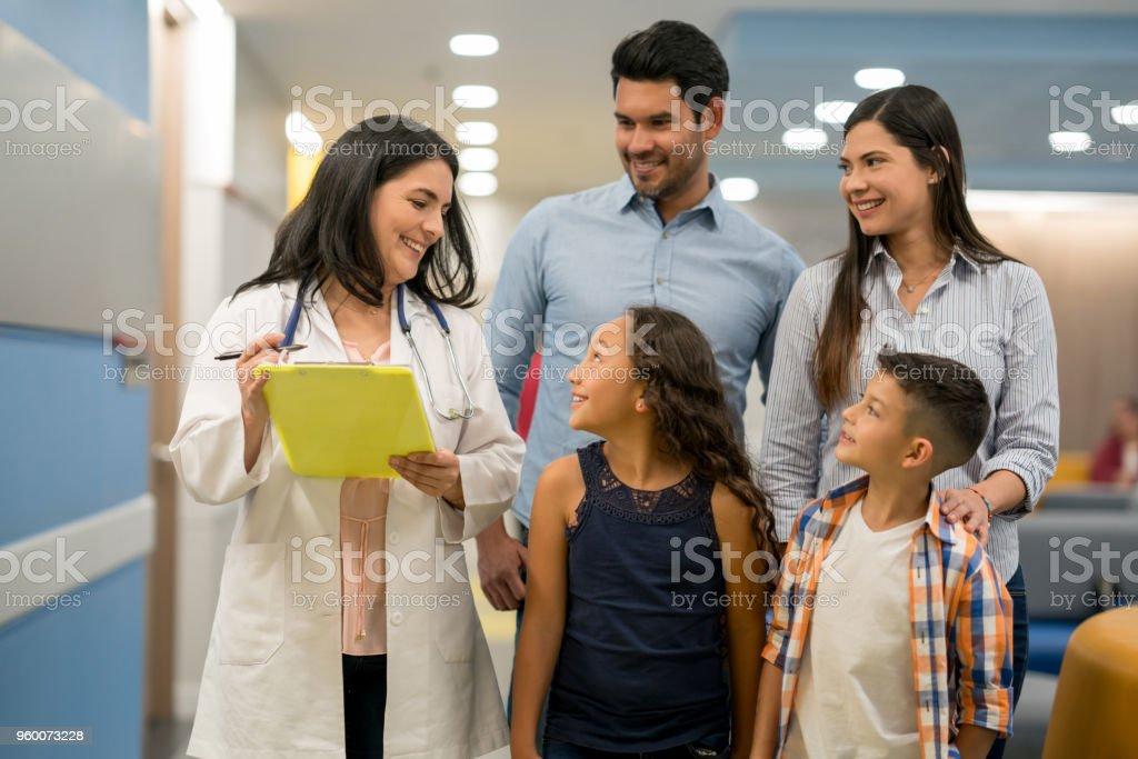 Weibliche Kinderarzt im Gespräch mit ihrer süßen Patientin während Bruder und Eltern alle lächelnd zuzuhören – Foto