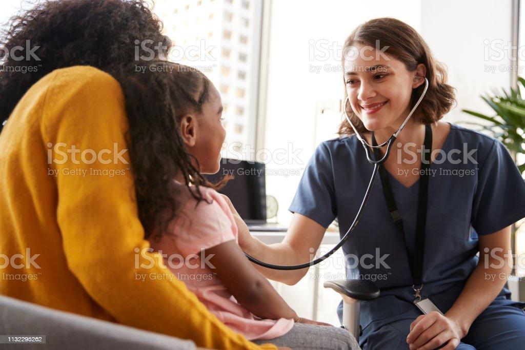 Weibliche Kinderärztin Wearing Scrubs Listening To Girls Chest mit Stethoskop Im Krankenhausbüro - Lizenzfrei Arzt Stock-Foto