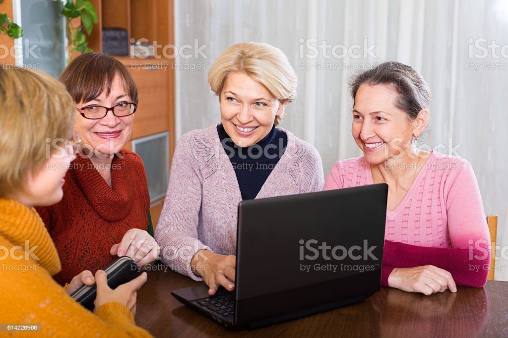 female pensioner studying laptop stock photo