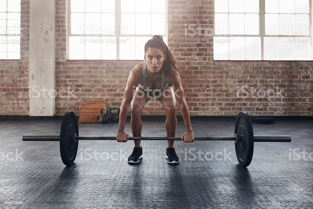 Female performing deadlift exercise with weight bar stock photo