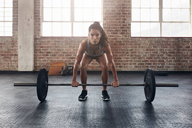 female performing deadlift exercise with weight bar - weights stock photos and pictures