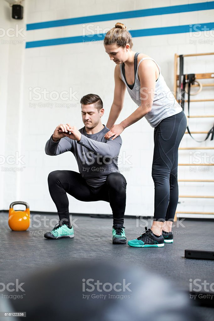 Female personal trainer guiding man at gym stock photo