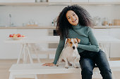Female pet owner expresses love to dog, dressed in casual turtleneck and jeans, sits at white bench against cozy kitchen interior, spends free time at home, smiles broadly from happy enotions