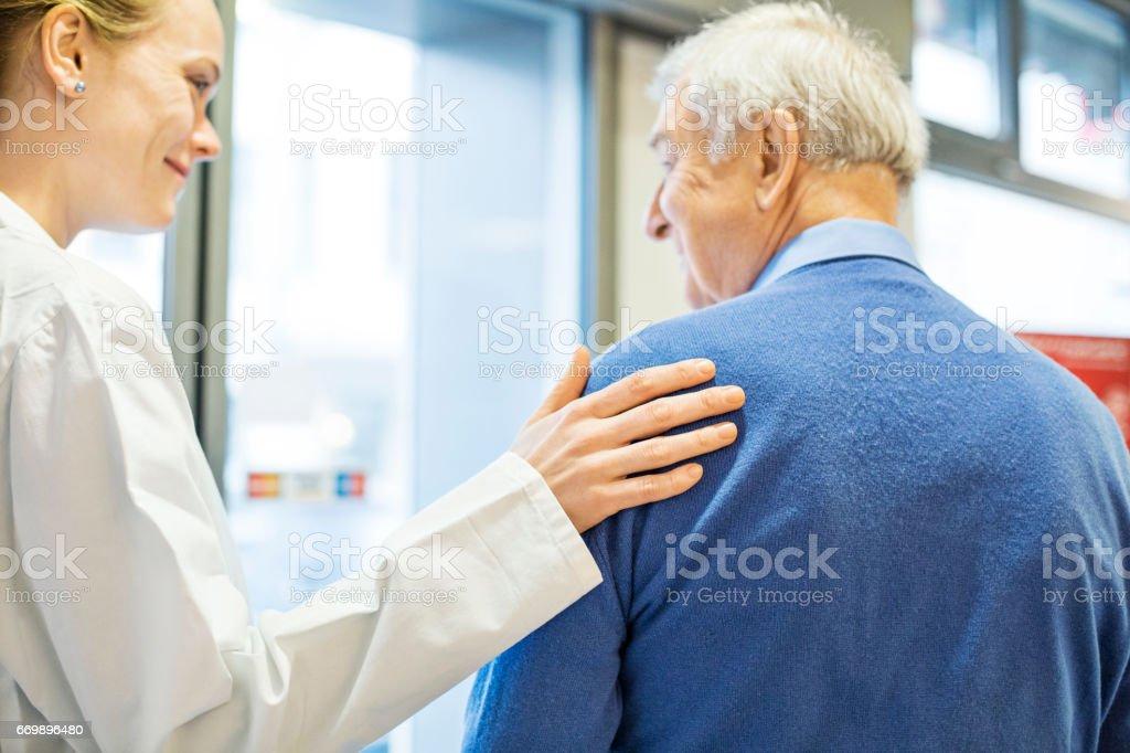 Female pharmacist consoling senior man stock photo