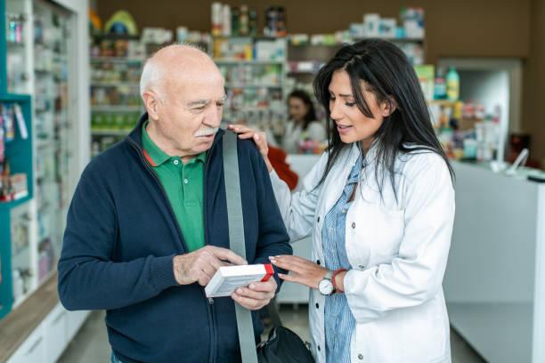 Female pharmacist giving medications to senior customer Female pharmacist giving medications to senior customer pharmacist stock pictures, royalty-free photos & images