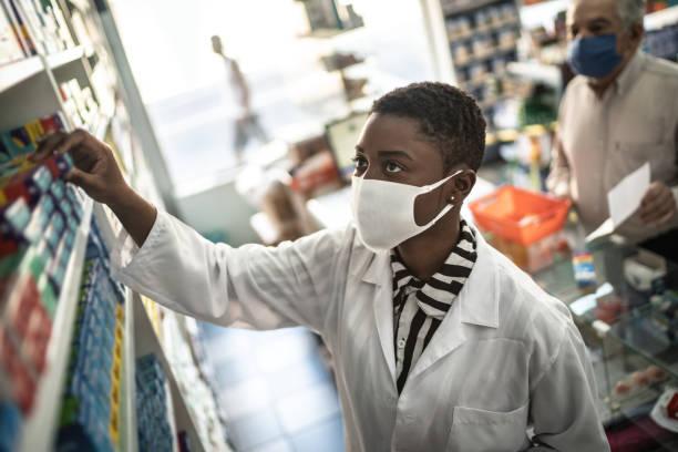 Female pharmacist giving medications to senior customer stock photo