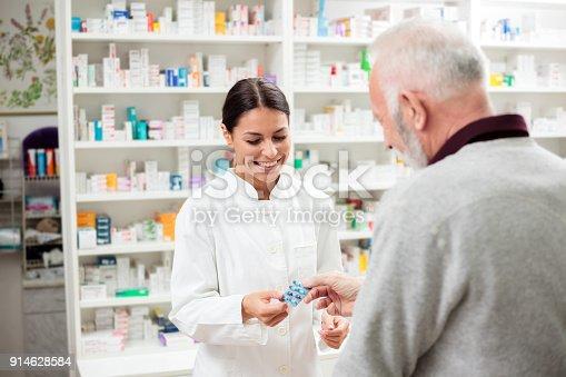 istock Female pharmacist giving medications to senior customer 914628584