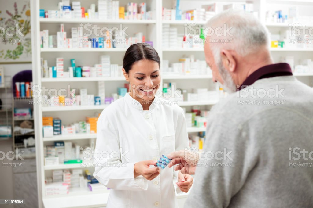 Female pharmacist giving medications to senior customer stock photo