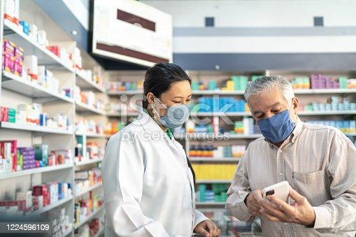 Female pharmacist helping a senior customer