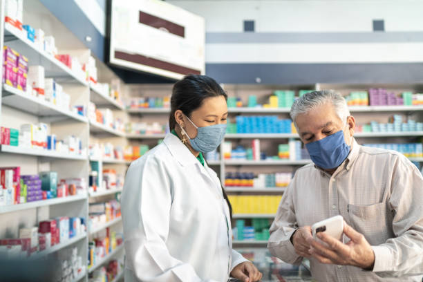 female pharmacist helping a senior customer - servizi essenziali foto e immagini stock