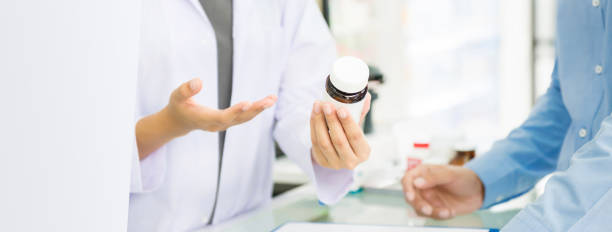 female pharmacist holding medicine bottle giving advice to customer in chemist shop or pharmacy - pharmacy stock pictures, royalty-free photos & images