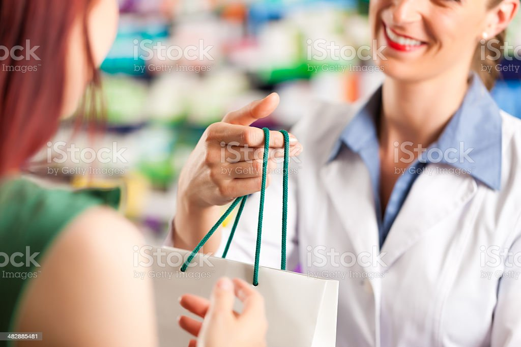 Female pharmacist in her pharmacy with a client royalty-free stock photo
