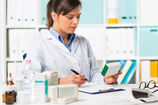 female pharmacist sat at desk writing notes - kosmetik testen stock-fotos und bilder