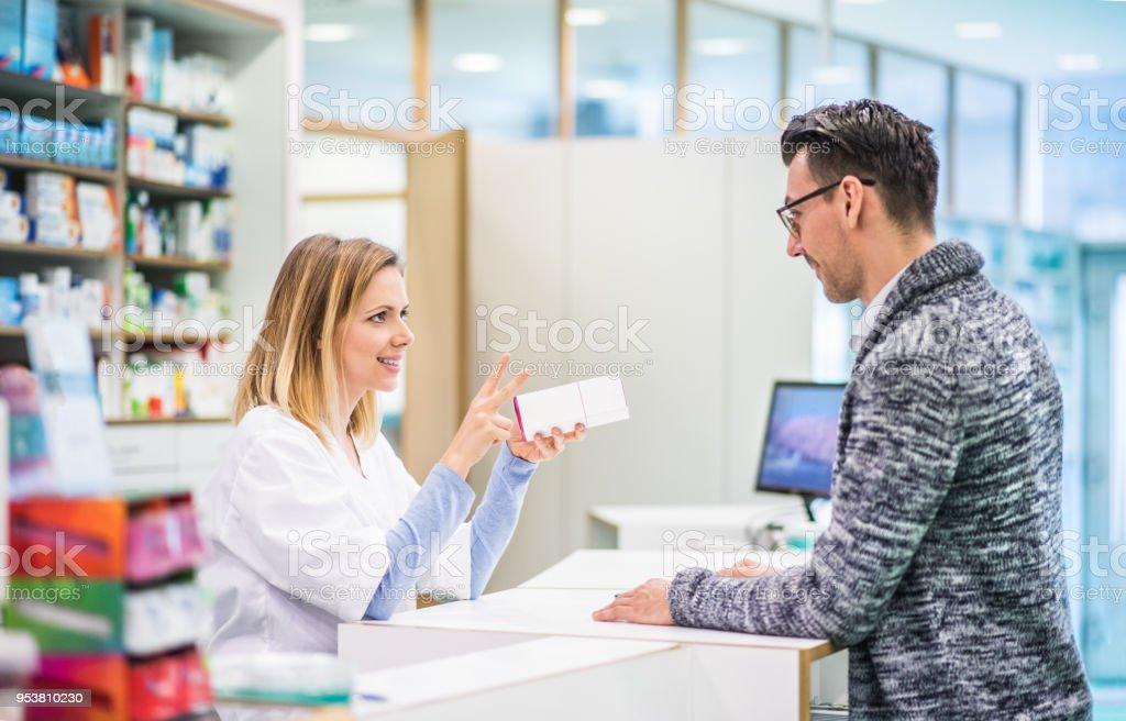 Female pharmacist serving a male customer. stock photo