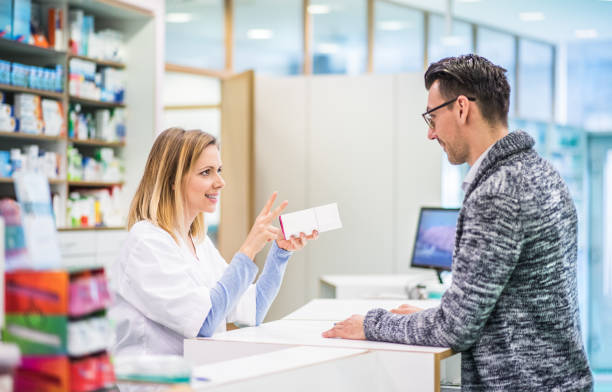 female pharmacist serving a male customer. - pharmacy stock pictures, royalty-free photos & images