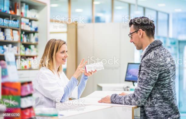 Female Pharmacist Serving A Male Customer - Fotografias de stock e mais imagens de Adulto