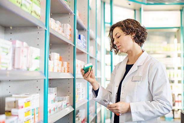 frau apotheker medikament nehmen vom regal - lieblingsrezepte stock-fotos und bilder