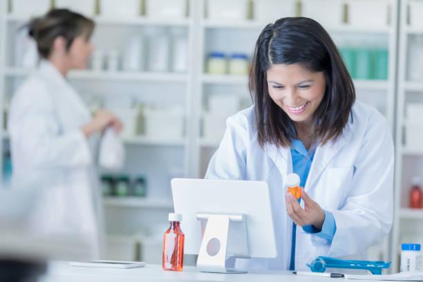 mujer farmacéutico utiliza computadora en la farmacia - farmacia fotografías e imágenes de stock