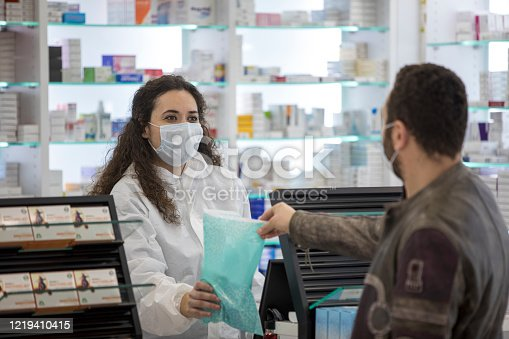 Female pharmacist wearing a surgical mask gives his medication to the patient