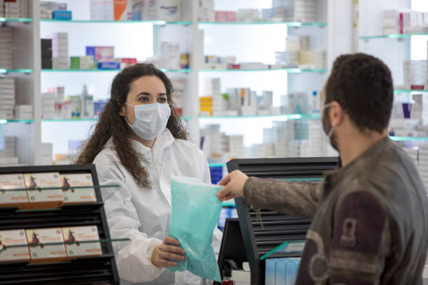 Female pharmacist wearing a surgical mask gives medication to the patient Female pharmacist wearing a surgical mask gives his medication to the patient pharmacy stock pictures, royalty-free photos & images