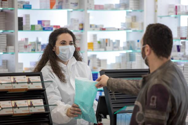 외과 용 마스크를 착용한 여성 약사가 환자에게 약을 제공합니다. - 약사 뉴스 사진 이미지