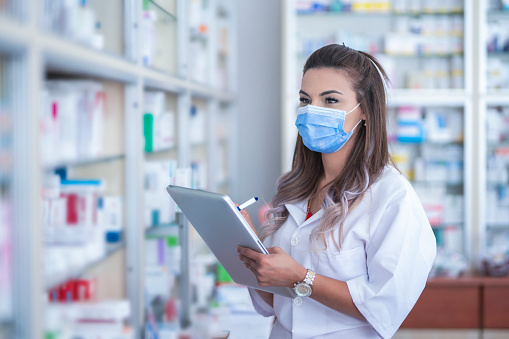 Female pharmacist with digital tablet wearing a medical mask