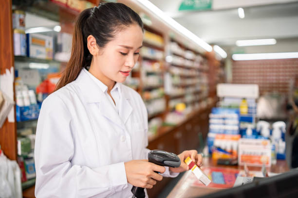 Female pharmacist working in a drug store stock photo
