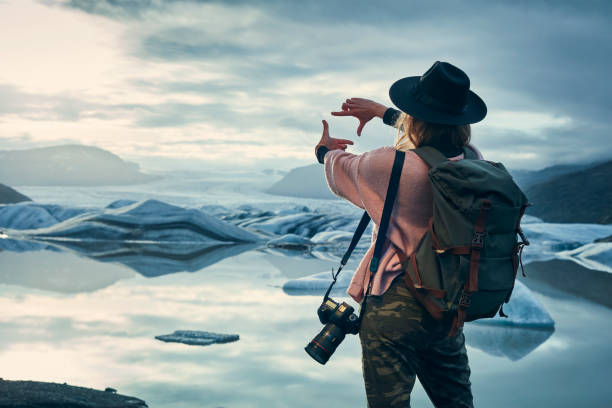 Female photographer at glacier lagoon. Sunset stock photo