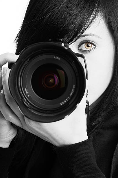 Female photographer in black and white holding a camera stock photo