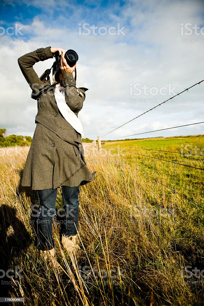 Female photographer on a fenced-in field composing photos stock photo