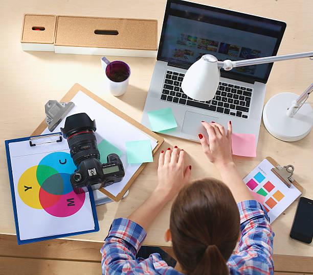 Weibliche Fotografen sitzend am Schreibtisch mit laptop – Foto