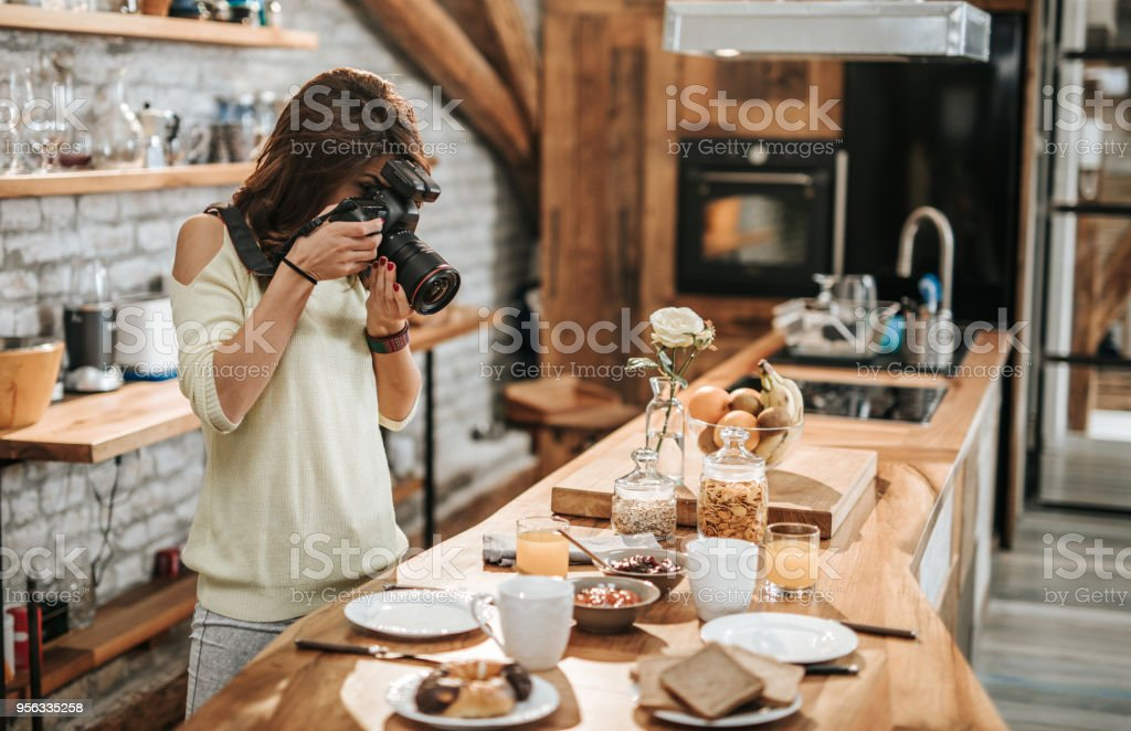 Female photographer taking photos of food at dining table. stock photo