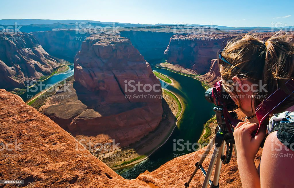 Female photographer taking shot of Horseshoe Bend, Grand Canyon stock photo