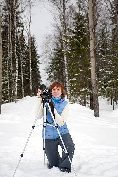 Female Photographer with Camera and Tripod stock photo