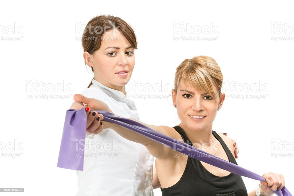 Female physical therapist helps patient in exercises with elastic band stock photo