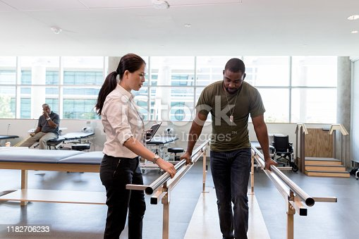 During the physical therapy session, the mid adult female therapist watches the mid adult male veteran grip the handrails and walk on his injured leg and foot.