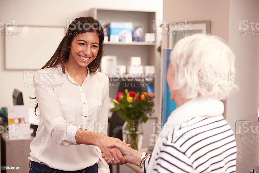 A female physician greeting an elderly woman in the office stock photo